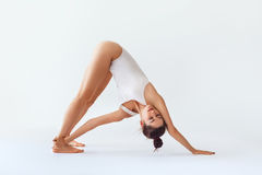 La jeune femme faisant l'asana de yoga a tourné l'isolat orienté vers le bas de chien image stock