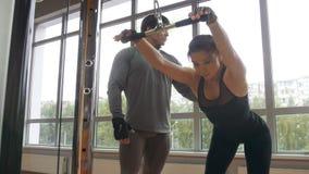 La jeune femme faisant la séance d'entraînement de crossfit a mené par l'entraîneur personnel photographie stock