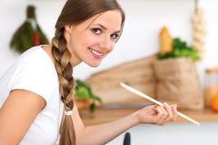 La jeune femme fait cuire dans une cuisine La femme au foyer goûte la soupe par la cuillère en bois Photos stock