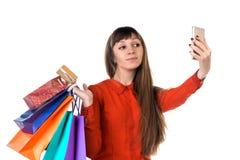 La jeune femme fait des emplettes avec la carte de crédit tenant des paquets faisant le selfie Photo libre de droits