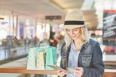 La jeune femme fait des emplettes en ligne Image stock