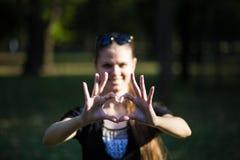 La jeune femme fait des mains dans la forme du coeur d'amour Photo stock