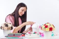 La jeune femme fait les fleurs artificielles Photo libre de droits