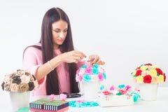 La jeune femme fait les fleurs artificielles Photographie stock libre de droits
