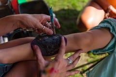La jeune femme fait un tatouage de pochoir à un jeune garçon photo libre de droits