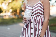 La jeune femme fascinante dans une robe rose rayée élégante pose en parc et prises dans des mains un milkshake doux photo libre de droits