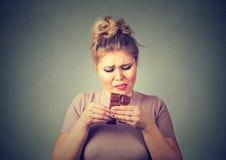 La jeune femme a fatigué des restrictions de régime implorant le chocolat de bonbons Photographie stock