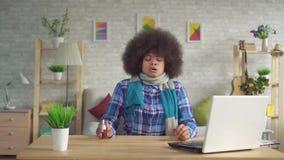 La jeune femme fatiguée d'Afro-américain de portrait avec la coiffure d'Afro avec l'écharpe sur le cou est malade, jet de nez d'u clips vidéos