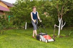 La jeune femme fauchent l'herbe Photo libre de droits