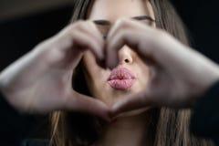 La jeune femme font le symbole de coeur avec des doigts et envoient un baiser Image stock