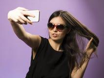 La jeune femme font Selfie dans des lunettes de soleil sur le fond pourpre La photo google dedans sur le plus défunt Iphone X image stock