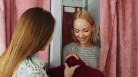 La jeune femme gaie apparaît par derrière le rideau de la cabine d'essayage tandis que l'employé de magasin donne son nouveau pul banque de vidéos