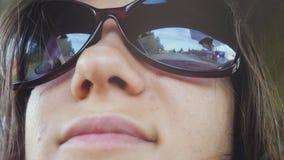 La jeune femme gaie utilise des lunettes de soleil se reposant dans le passager de voiture regardant la fenêtre le jour ensoleill Photos stock