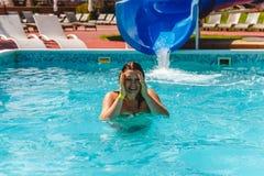 la jeune femme glissée le waterslide dans la piscine et les rires photos stock