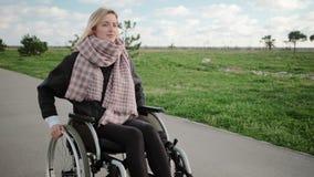 La jeune femme handicapée monte sur le fauteuil roulant dans le secteur de parc chronomètrent au printemps banque de vidéos