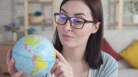 La jeune femme haute étroite étudie le globe, le tenant banque de vidéos