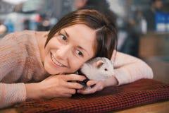 La jeune femme heureuse étreint son furet d'animal familier Image libre de droits
