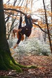 La jeune femme heureuse accrochant sur l'iand d'arbre rit des bois de n avec le sac à dos orange Fille drôle dupant autour sur un photo stock