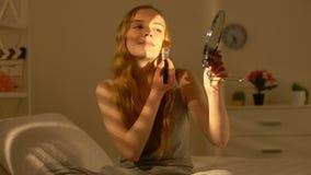 La jeune femme heureuse appliquant le maquillage rougissent souriant sur la caméra, beauté naturelle banque de vidéos