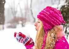 La jeune femme heureuse apprécient la neige en parc de ville d'hiver extérieur Photographie stock