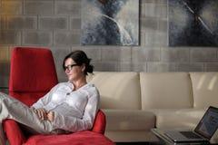 La jeune femme heureuse détendent à la maison sur le sofa photos stock