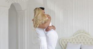 La jeune femme heureuse d'étreinte de couples courent et sautent par-dessus la chambre à coucher à la maison moderne de l'homme banque de vidéos