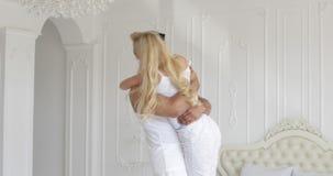 La jeune femme heureuse d'étreinte de couples courent et sautent par-dessus la chambre à coucher à la maison moderne de l'homme clips vidéos
