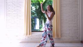La jeune femme heureuse dans des pyjamas danse à côté de la fenêtre avec le téléphone portable écoute la musique chante apprécier banque de vidéos