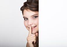 La jeune femme heureuse de sourire se tenant derrière et se penchant sur un panneau d'affichage ou une plaquette vide blanc, expr Image stock