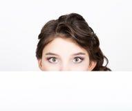 La jeune femme heureuse de sourire se tenant derrière et se penchant sur un panneau d'affichage ou une plaquette vide blanc, expr Image libre de droits