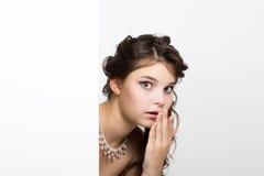 La jeune femme heureuse de sourire se tenant derrière et se penchant sur un panneau d'affichage ou une plaquette vide blanc, expr Photos stock