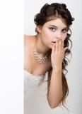 La jeune femme heureuse de sourire se tenant derrière et se penchant sur un panneau d'affichage ou une plaquette vide blanc, expr Photo stock