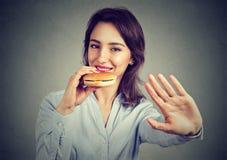 La jeune femme heureuse dit non de suivre un régime des restrictions appréciant son cheeseburger Images libres de droits