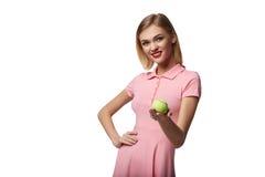 La jeune femme heureuse en bonne santé pose tout en tenant la balle de tennis, sur le wh Image stock