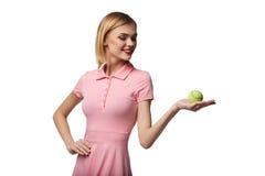 La jeune femme heureuse en bonne santé pose tout en tenant la balle de tennis, sur le wh Photographie stock libre de droits