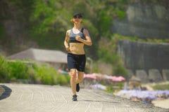 La jeune femme heureuse et attirante de coureur de sport faisant pulser dehors courant de séance d'entraînement d'isolement sur l image libre de droits