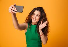 La jeune femme heureuse font le selfie saluant des amis Photos libres de droits