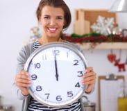 La jeune femme heureuse montrant l'horloge dans Noël a décoré la cuisine Photo libre de droits