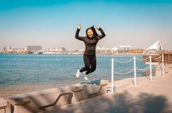 La jeune femme heureuse saute dans le ciel Images libres de droits