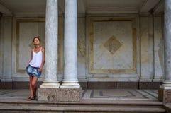 La jeune femme heureuse se tient entre de vieux et grands piliers photographie stock