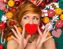La jeune femme heureuse se trouvant avec Noël rouge 2016 de coeur a enveloppé le gi Photographie stock libre de droits