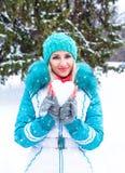 La jeune femme heureuse tenant le coeur de neige et apprécient en parc de ville d'hiver extérieur Photos libres de droits