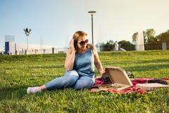 La jeune femme heureuse tenant la pizza chaude dans la boîte, posent extérieur en parc photos stock