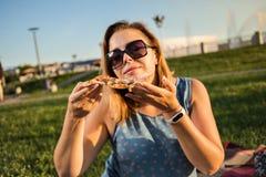La jeune femme heureuse tenant la pizza chaude dans la boîte, posent extérieur en parc photo libre de droits