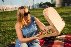 La jeune femme heureuse tenant la pizza chaude dans la boîte, posent extérieur en parc photographie stock