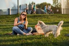 La jeune femme heureuse tenant la pizza chaude dans la boîte, posent extérieur en parc photos libres de droits