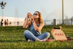 La jeune femme heureuse tenant la pizza chaude dans la boîte, posent extérieur en parc image libre de droits