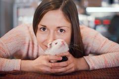 La jeune femme heureuse tient son furet d'animal familier Photographie stock