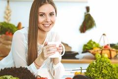 La jeune femme heureuse tient la tasse blanche et regarde l'appareil-photo tout en se reposant ? la table en bois dans la cuisine images libres de droits