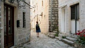 La jeune femme heureuse voyageant chez Monténégro et regardant les points de repère de Perast, fille de hippie avec la carte au c banque de vidéos